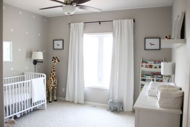 a gender neutral nursery done in grey and white, with elegant white furniture, a polka dot wall and open shelves with books