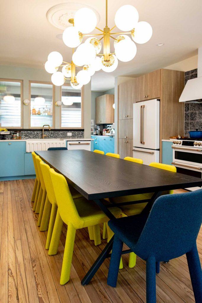 The eat-in kitchen shows off blue and white cabinets, a wooden dining table and yellow and navy chairs