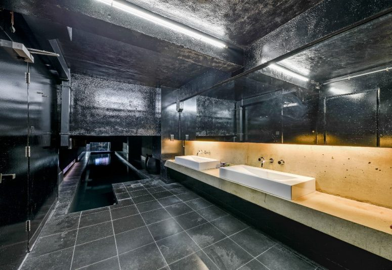 The bathroom is all black, with a stone vanity and tiles and other surfaces in black