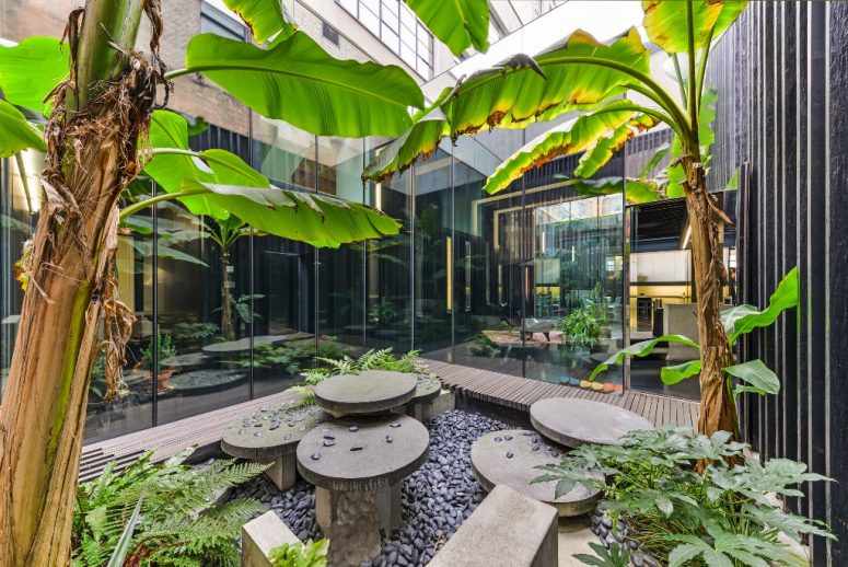 An inner courtyard is like a garden, with tropical trees, pebbles and some stone furniture