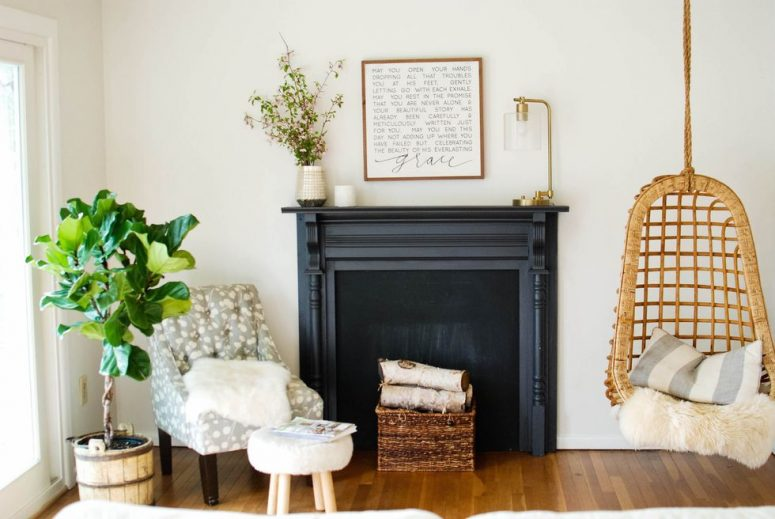 a black faux fireplace with a refined mantel, a basket with wooden logs is a stylish rustic idea to go for