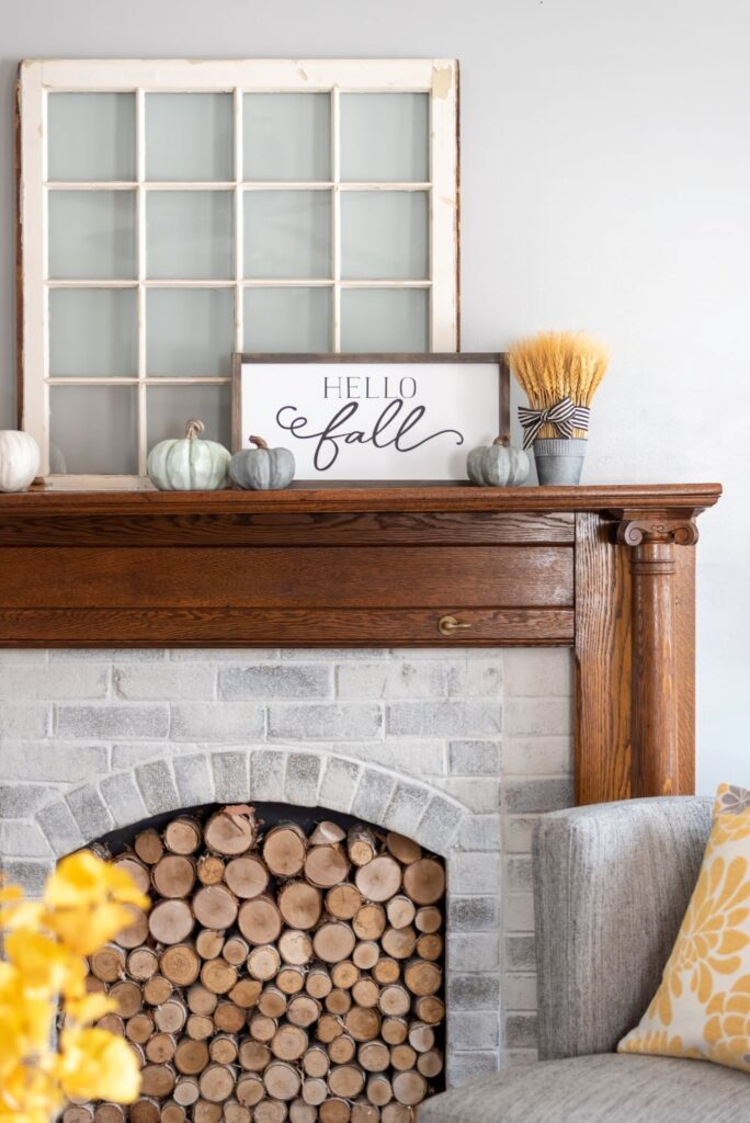 a farmhouse fireplace with a whitewashed brick surround, a stained wooden mantel and with firewood inside it