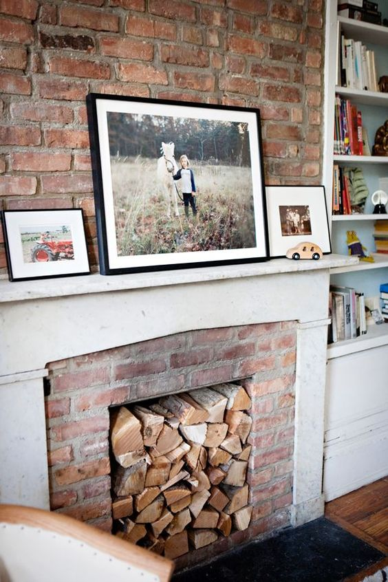a rustic fireplace of red brick, with a white mantel and some firewood inside the fireplace plus photos on the mantel