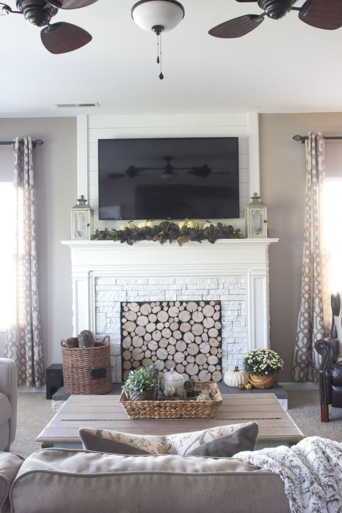 a rustic fireplace clad with white faux fur, a faux mantel and with logs inside for a modern farmhouse living room