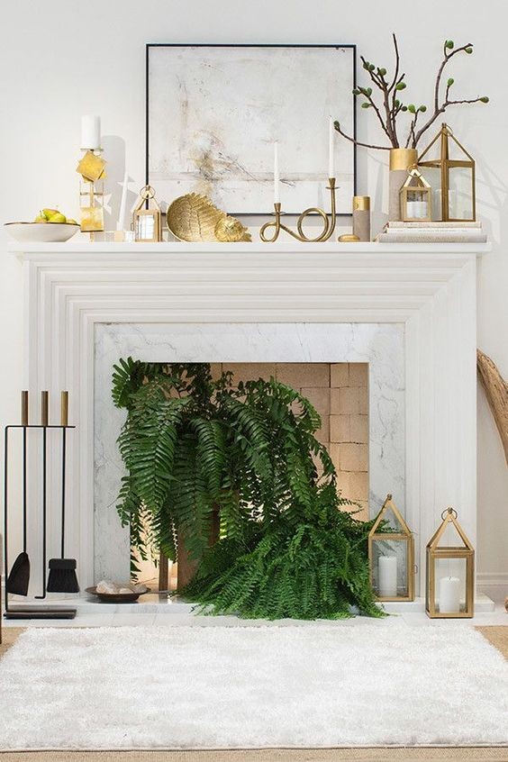 a non-working fireplace with potted ferns, candle lanterns, lights and gold candle lanterns and decor on the mantel