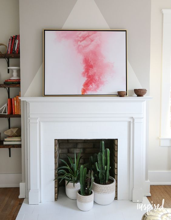 a non-working brick fireplace with a white surround and mantel plus cacti and succulents in pots inside it is wow