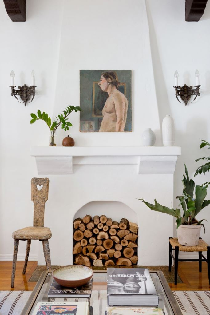 a stylish white non-working fireplace with very natural firewood inside is a chic idea with a rustic feel