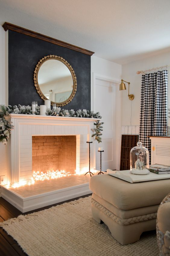 a winter non-working fireplace with lights inside it, snowy fir garland, candles and a mirror over the mantel