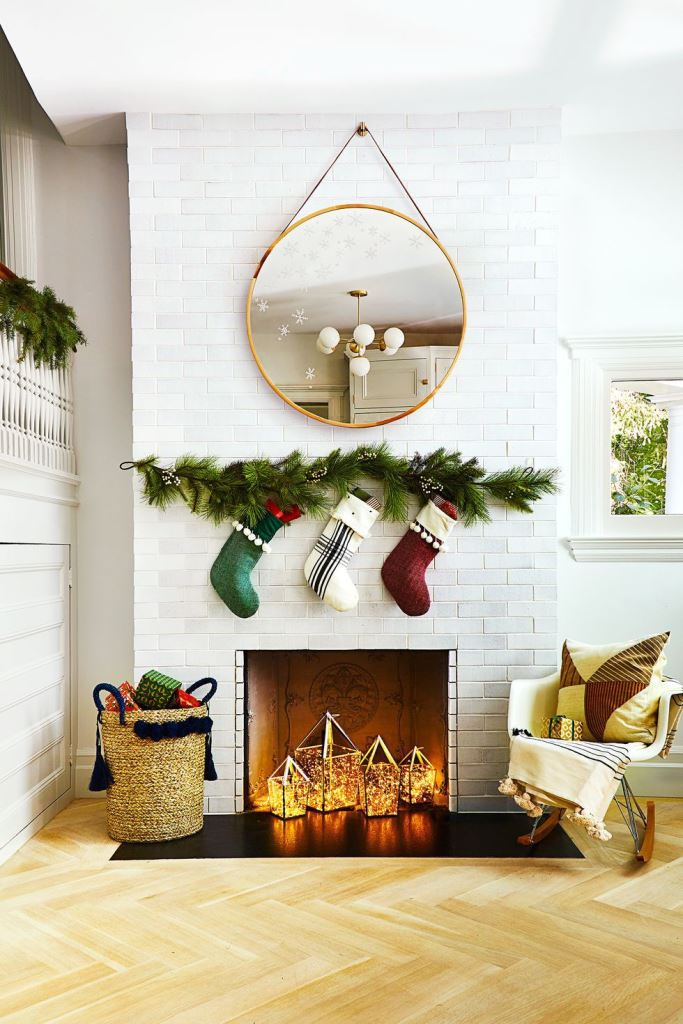 a non-working fireplace styled for Christmas with some stockings hanging over it and with lights lanterns inside it