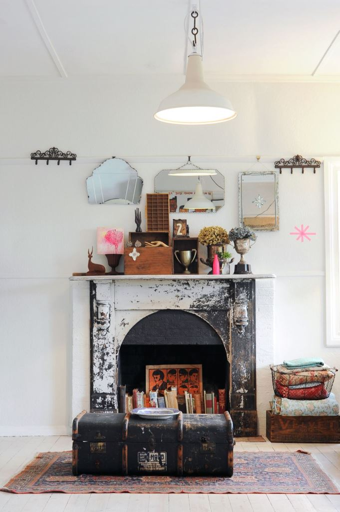 a shabby cihc fireplace with books and a bold artwork looks statement-like and bold, a suitcase in front of it adds vintage charm