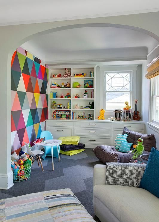 an ultimate playroom with a colorful statement wall, a neutral storage unit, some comfy chairs is very cool
