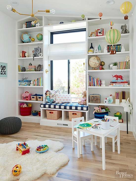 a vivacious playroom with open storage spaces, a windowsill bench, white furniture and colorful toys and books