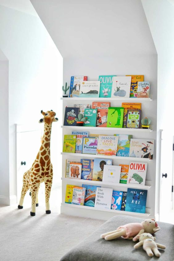 a comfy space for reading - ledges with colorful kid books and a soft seat with toys