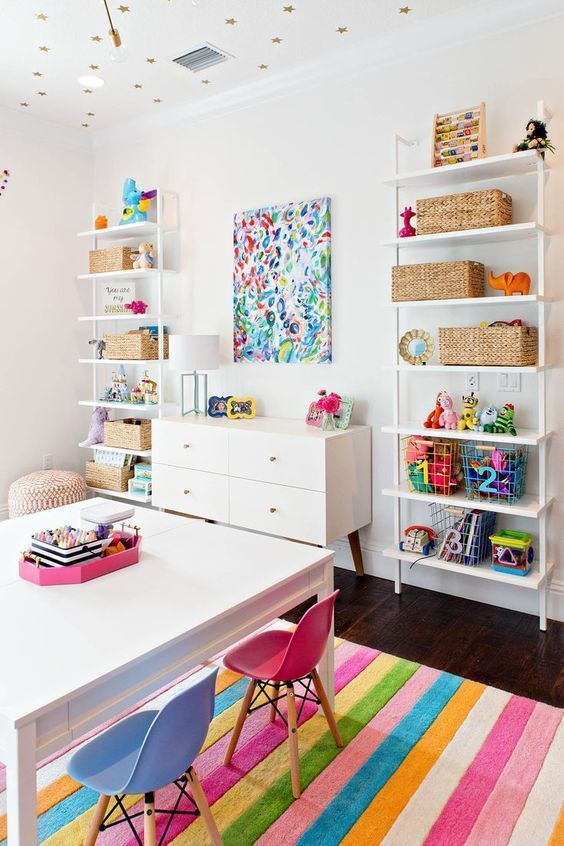 a colorful and bold playroom with open storage units, a bold artwork and bright rug, furniture and accessories