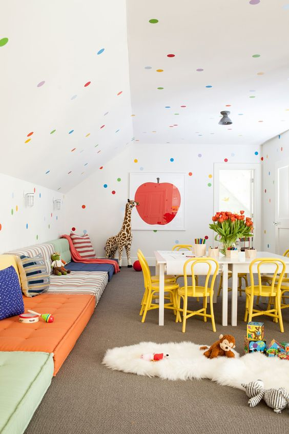 a fun and bold kids' playroom with sofas lining up the wall, a creativity zone, polka dot walls and a ceiling and bright toys