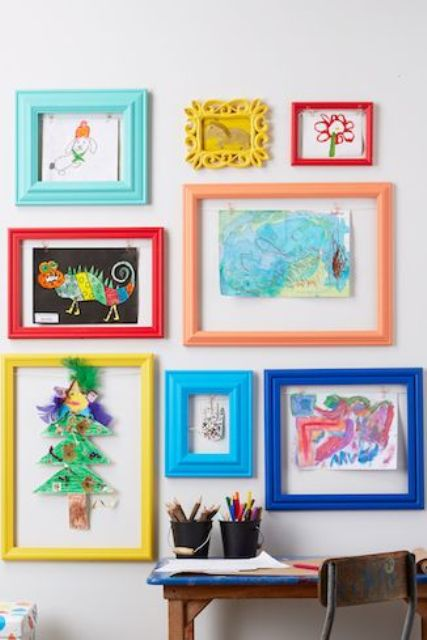 a colorful gallery wall with kids' artworks placed into colorful frames is a bold decor idea to rock