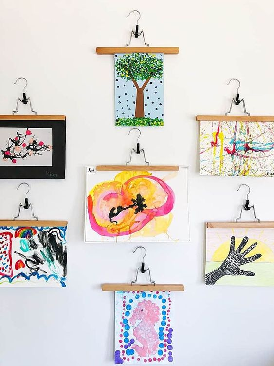 a bold gallery wall with lots of kids' artworks hanging is a creative and chic idea to try