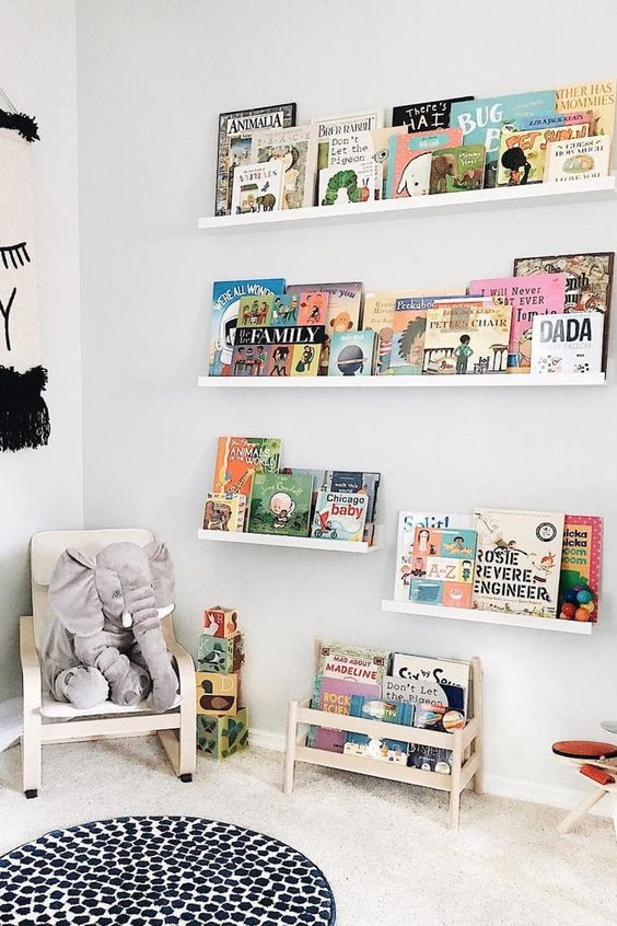 a contemporary reading nook with white and light stained furniture, bold books and toys