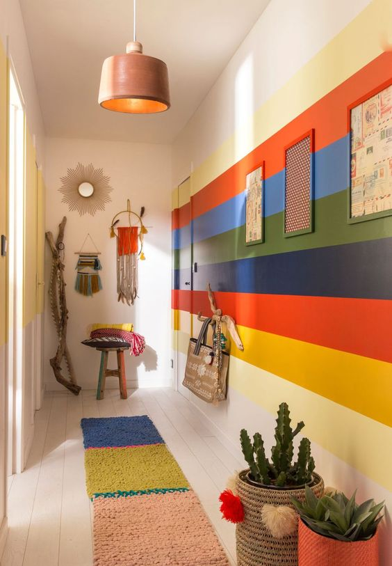 a colorful boho entryway with a rainbow accent wall, a bold rug, pendant lamps and hangings plus planters