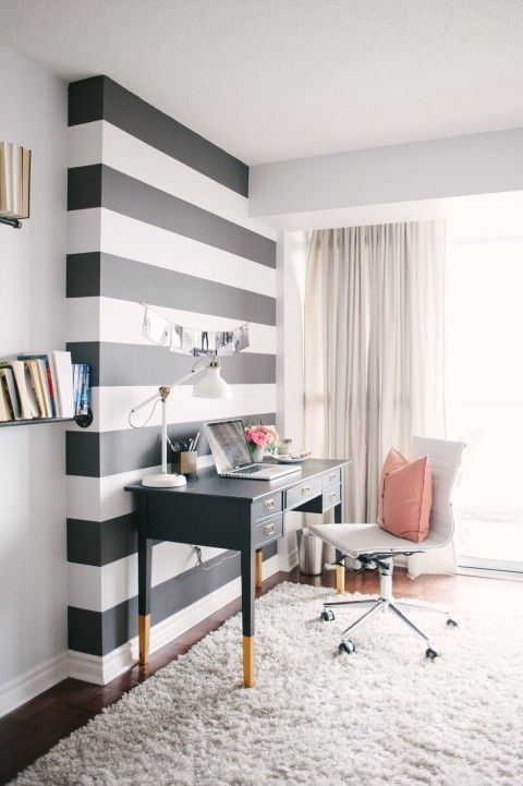 a light-filled home office with a black and white striped accent wall, a black desk, a white chair, neutral textiles and pink touches is very chic