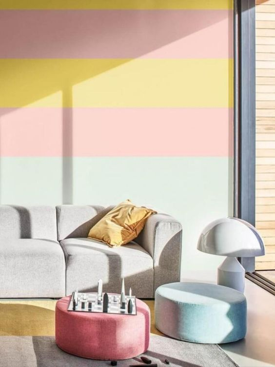 a colorful living room with a bold striped wall, a grey sofa, pastel ottomans and a floor lamp is very welcoming