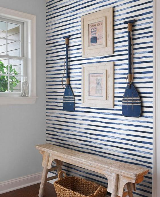 a coastal entryway with blue watercolor stripes, artworks and oars, a wooden bench and a basket is very bold