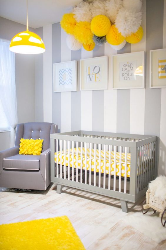 a bold grey, white and yellow nursery with a vertical stripe wall, a paper pompom arrangement, a grey chair and a yellow lamp