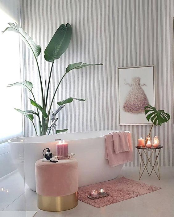 a charming girlish bathroom with a striped grey and white wall, a pink ottoman, a refined table and pink textiles