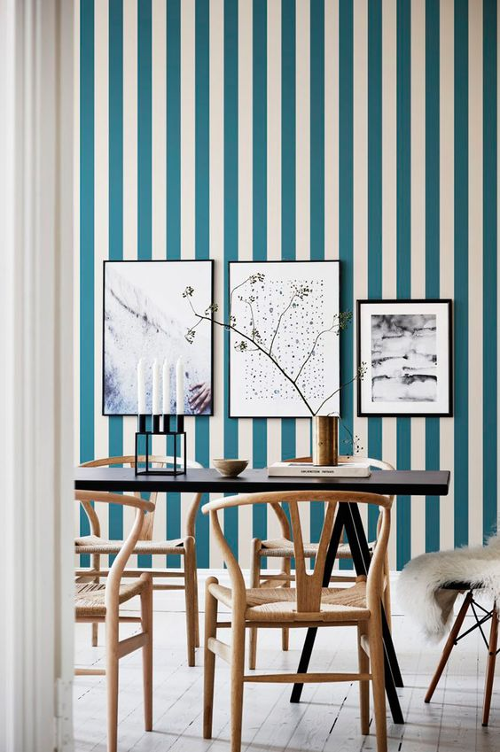 a chic dining room with a blue and white striped wall, a gallery wall, a black table and refined wooden chairs