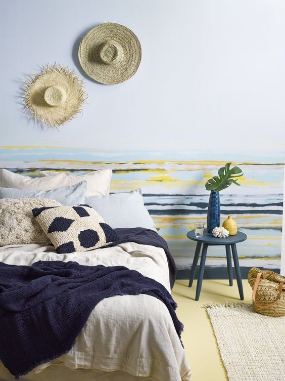 a beachy bedroom in bold colors - blue, navy, yellow, with a large comfy bed, a striped accent wall, knit and crochet bedding and rugs