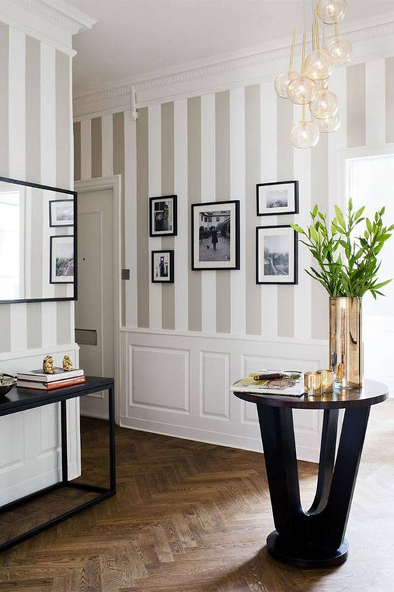 an art decor entryway with a grey and white striped wall, white paneling, a stylish gallery wall and dark furniture
