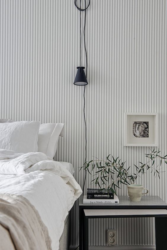 a Scandinavian bedroom finished off with a grey and white striped wall, a bed and a nightstand, some greenery and art is welcoming