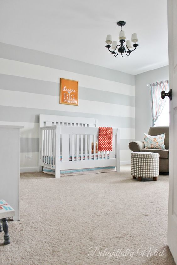 a neutral and very simple nursery with a grey and white striped wall, a retro chandelier, a crib and an ottoman
