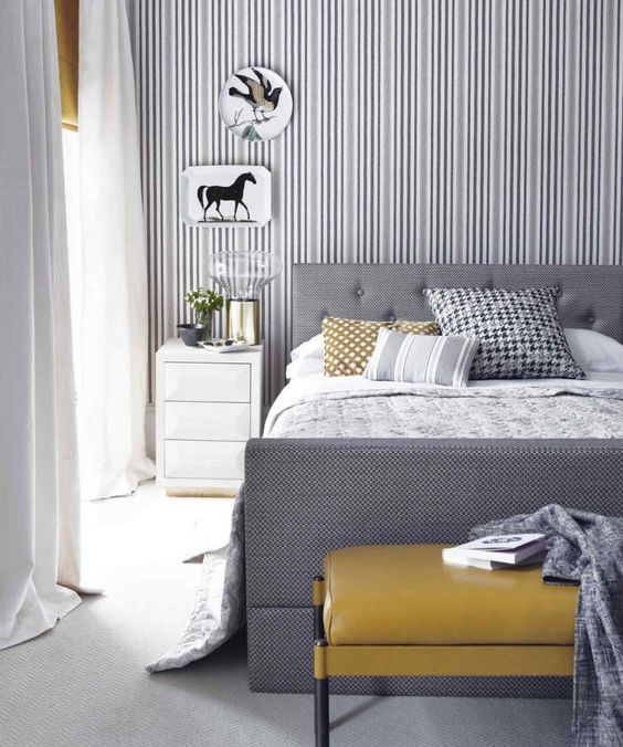 a stylish grey and white bedroom with a striped accent wall, a grey bed, a mustard ottoman and artworks