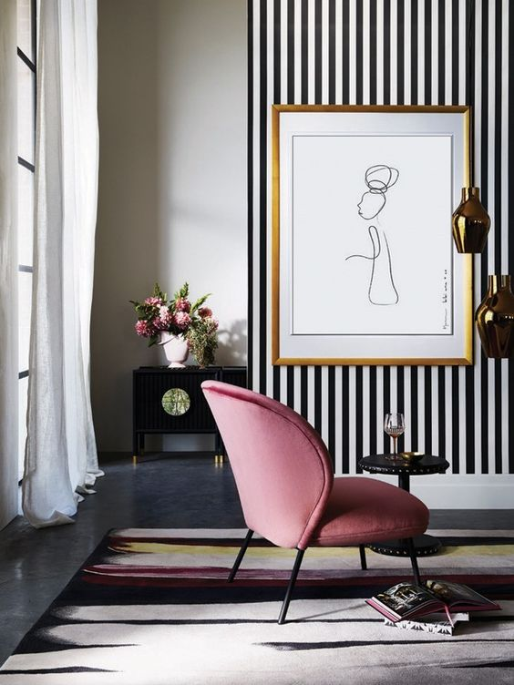 a sophisticated living room with a black and white accent wall, a pink chair and a pretty artwork and refined furniture