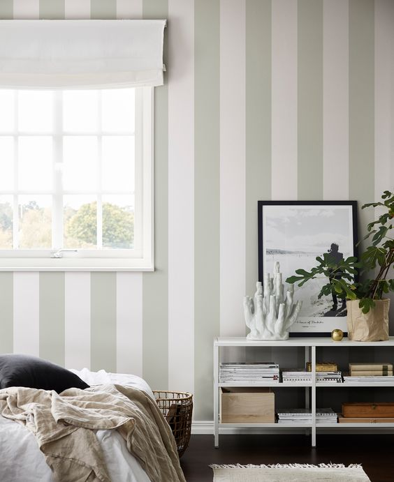 a neutral and ethereal bedroom with a green and white striped wall, neutral textiles and potted plants is very beautiful