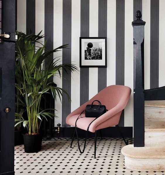 a refined entryway with a striped black and white accent wall and a matching printed monochromatic floor is pure chic