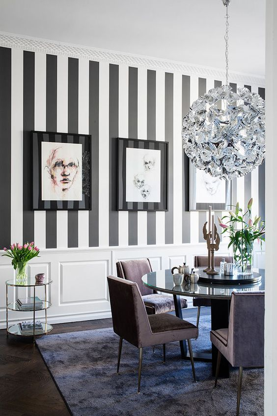 an exquisite dining room with a striped black and white wall, a chic shiny chandelier, lavender chairs and a mirror table