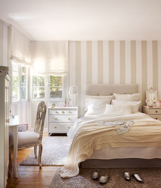 a neutral serene bedroom with a tan and white accent wall, neutral textiles and refined furniture is very welcoming
