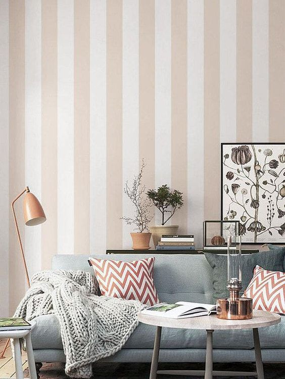 a neutral and welcoming living room with a striped tan and white accent wall that gives a subtle touch of color and print