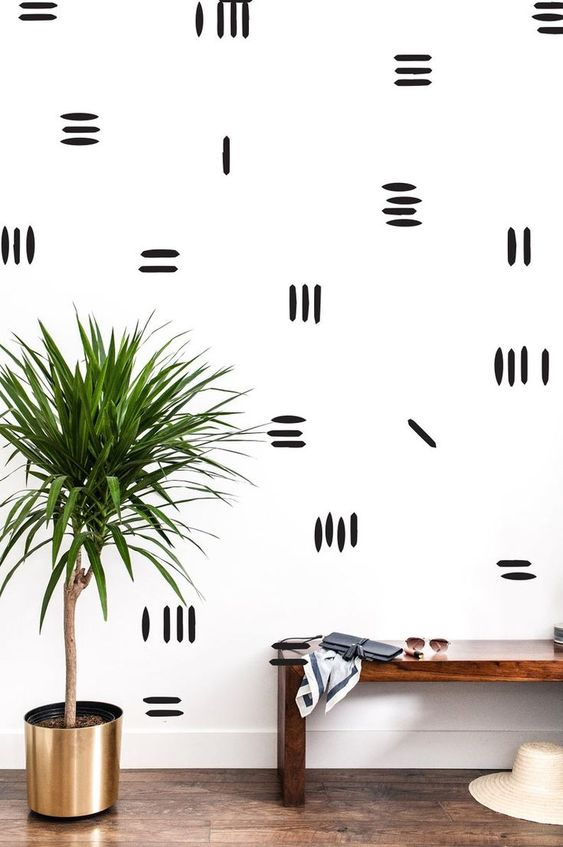a boho entryway with a monochromatic accent wall with stripes is a bright and fun idea for a modern space