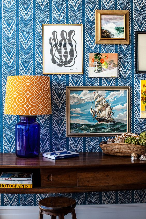 refined bold blue and white printed wallpaper and a gallery wall on it plus a printed lamp for a bright and eye-catchy nook