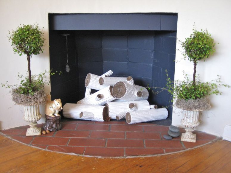 a fireplace clad with black matte tiles, with funny faux logs, topiaries on both sides and some pebbles