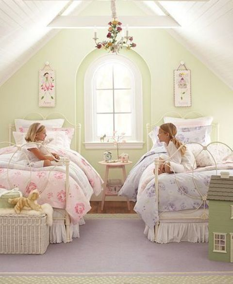 a pastel vintage shared bedroom with a green accent wall, white metal beds, a basket, a floral chandelier and floral bedding