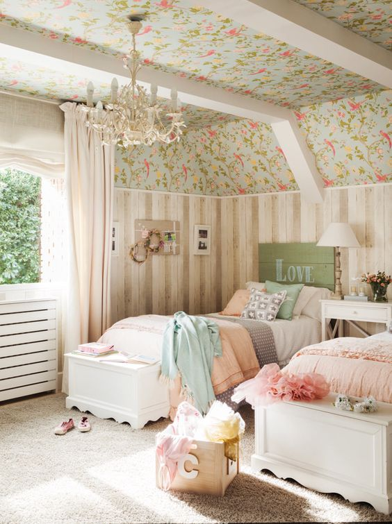 a shabby chic kids' room with floral wallpaper and wood paneling, white vintage furniture, pastel bedding and a chic chandelier
