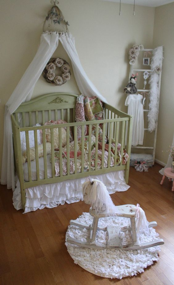 a shabby chic kid's room with light green walls, a green crib with a canopy, floral bedding, a ladder for storage, fabric flowers and vintage toys