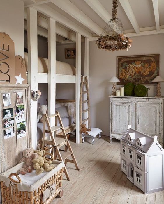 a shabby chic kid's room with dove grey walls, shabby chic furniture, lamps, a floral chandelier, toys in baskets