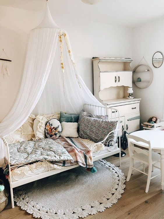 a shabby chic meets boho kid's room with neutral walls, white vintage furniture, pretty bright bedding and pillows and a canopy over the bed