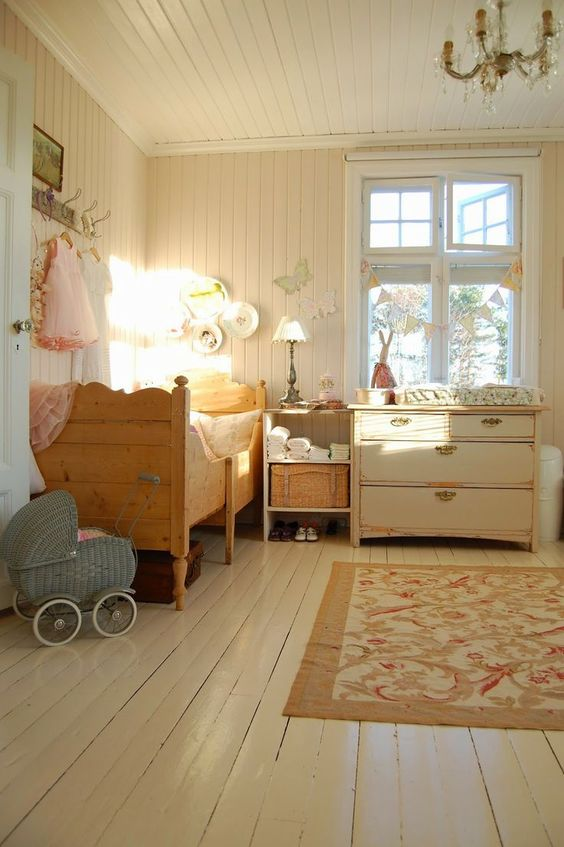 a rustic shabby chic kids' bedroom with vintage furniture, a crystal chandelier, a floral rug and baskets plus decorative plates