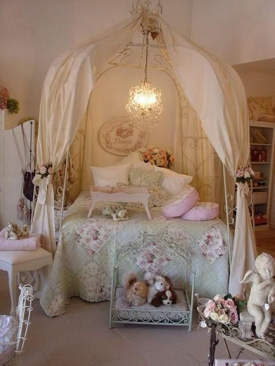 a shabby chic kids' room with a metal canopy bed, faux blooms everywhere, floral bedding and pretty vintage furniture
